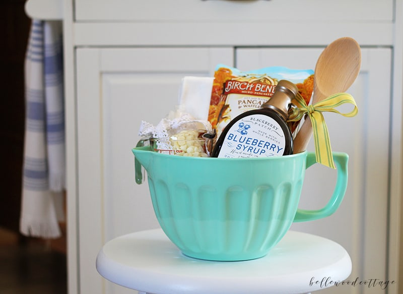 A green batter bowl filled with items to create a bridal shower gift basket.