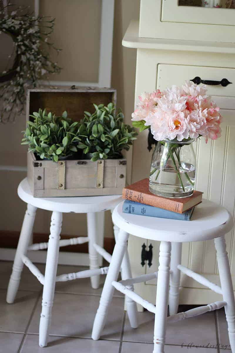 Farmhouse stools painted white and distressed with decorative greenery on top.