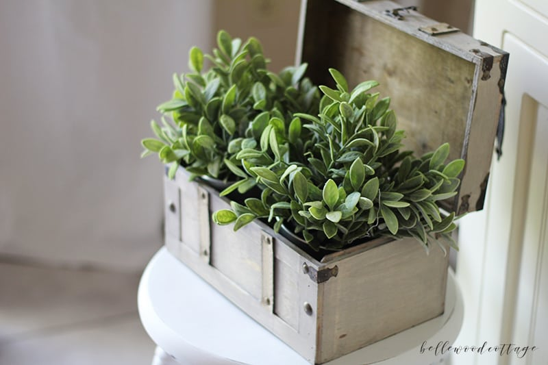 Greenery in a wooden box on top of a white painted stool.