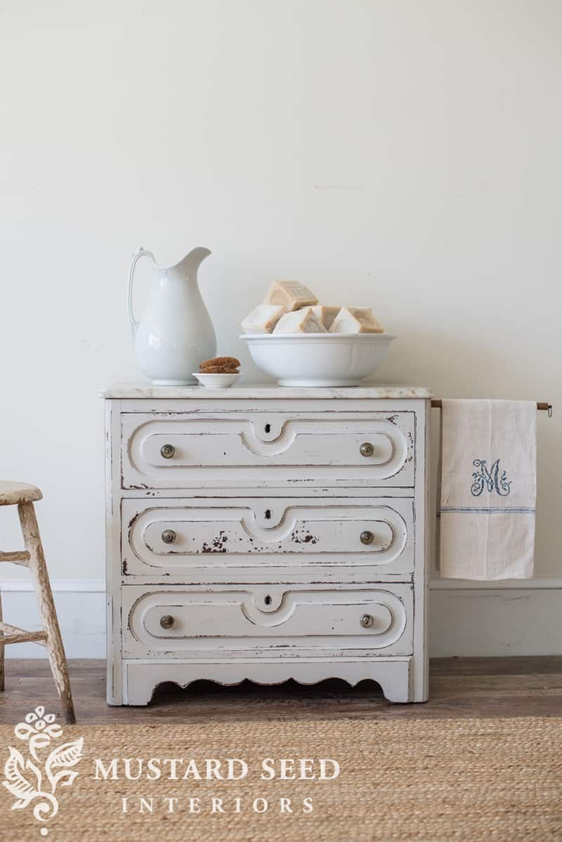 A white ironstone pitcher on an antique washstand.