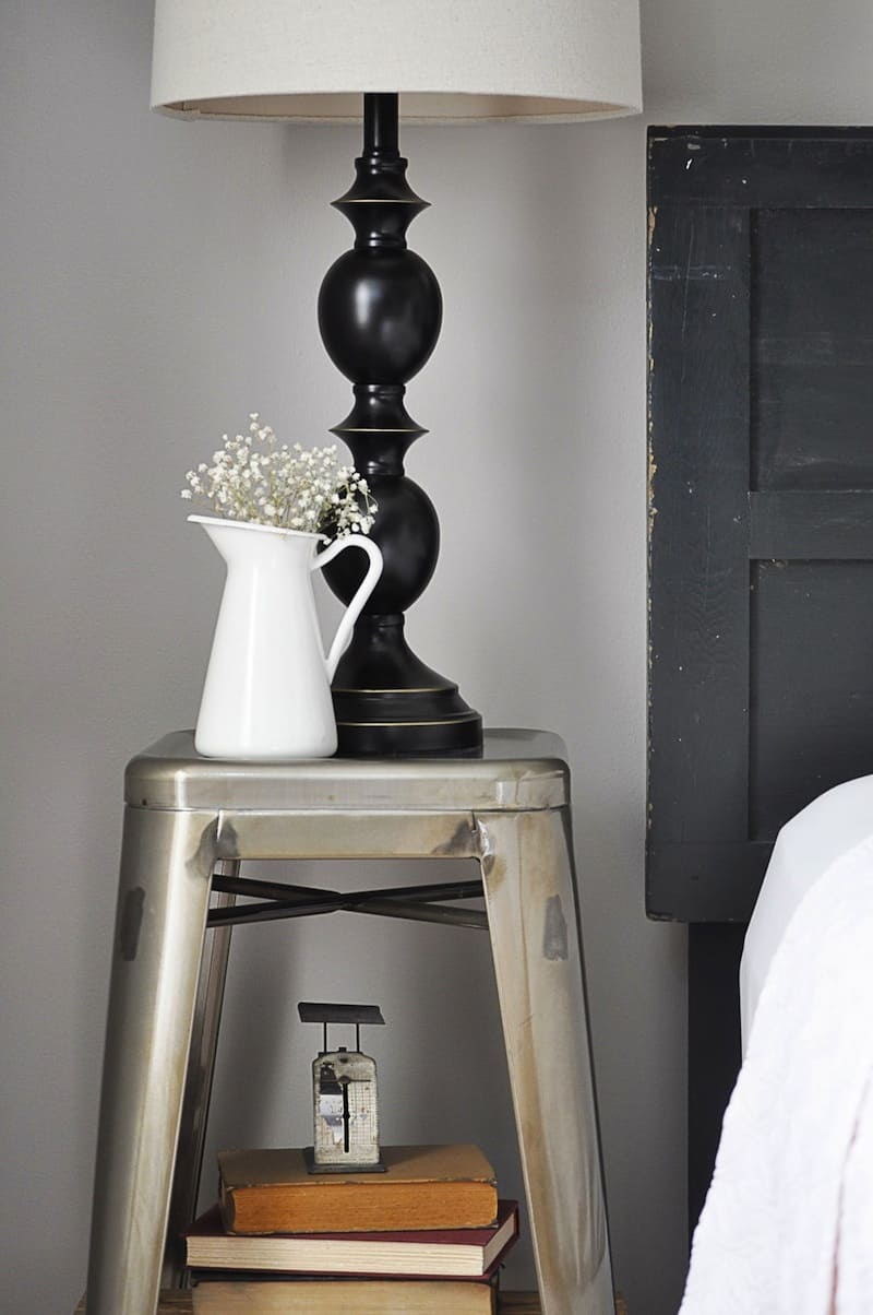 A nightstand display with a lamp and flowers.
