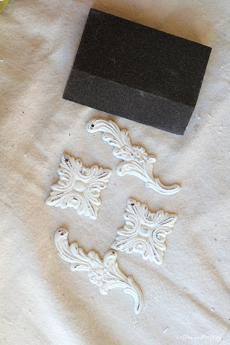 Lightly distressing chalk painted Christmas tree ornaments with a sanding block.