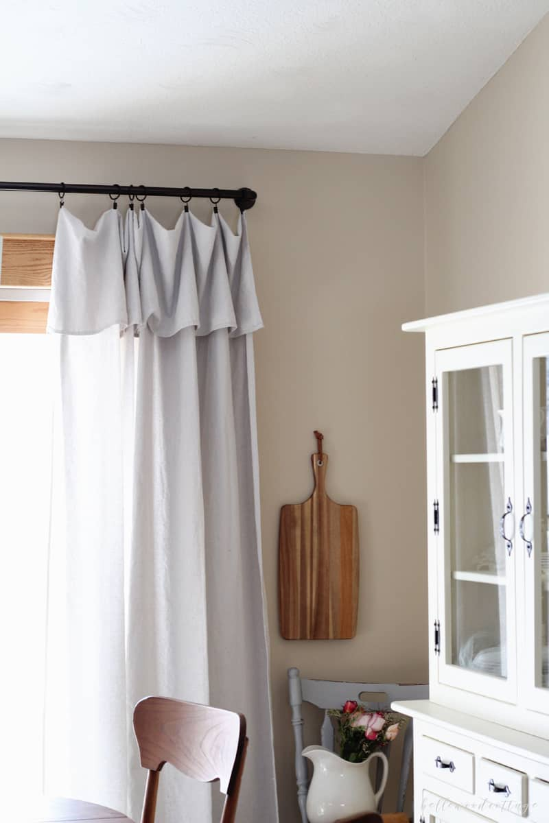 Unbleached drop cloth curtains hanging in a dining room.