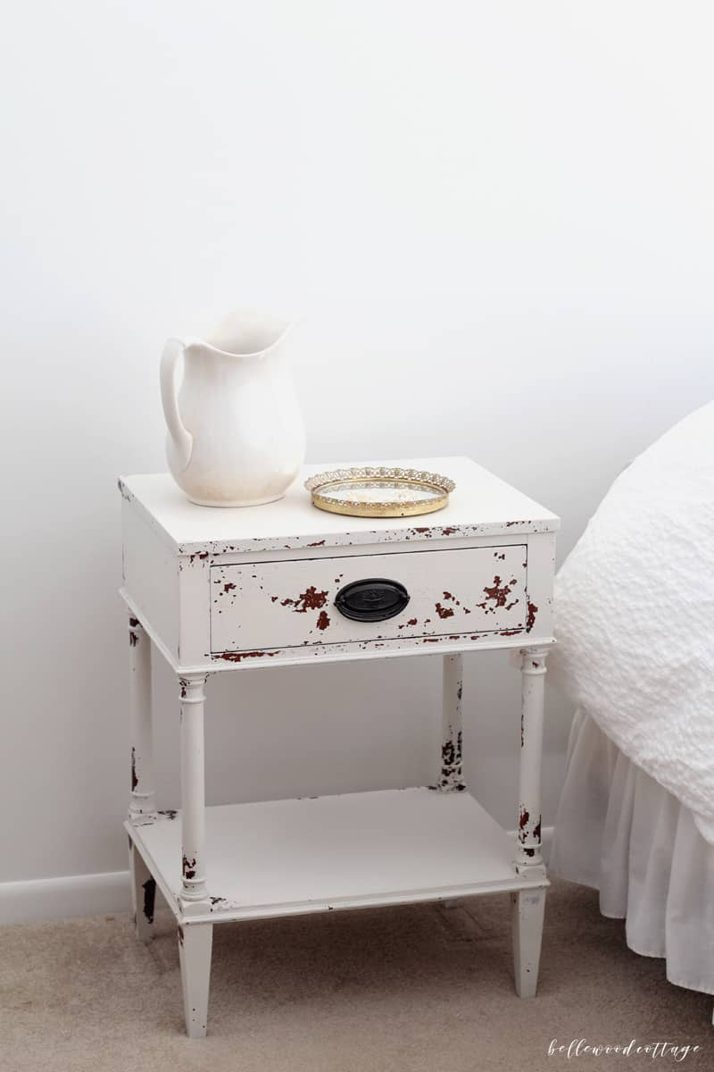 A nightstand with a white pitcher.