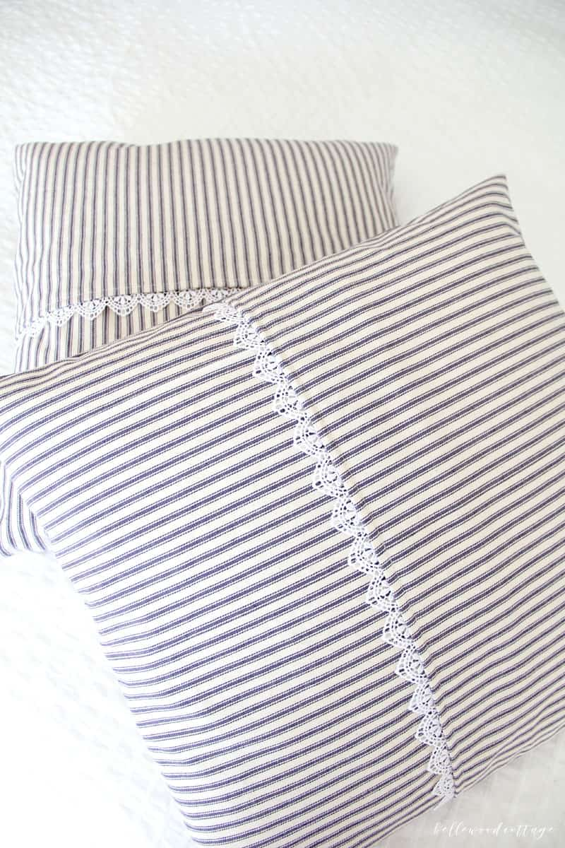 Learn how I made these farmhouse inspired ticking pillow covers over at Bellewood Cottage blog! They are so simple, easy, and inexpensive (total win). Add authentic farmhouse style to YOUR home with this quick project to make your own ticking pillow covers.