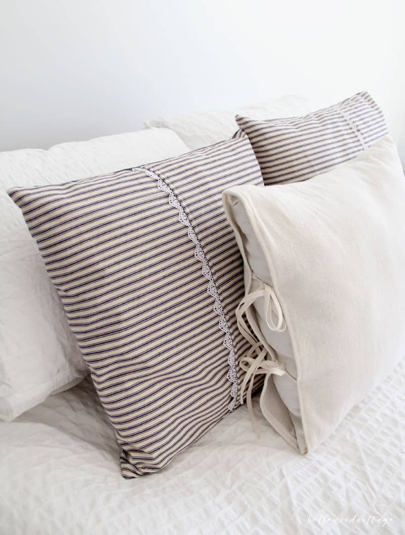 Ticking stripe pillows and drop cloth pillows arranged on a bed.