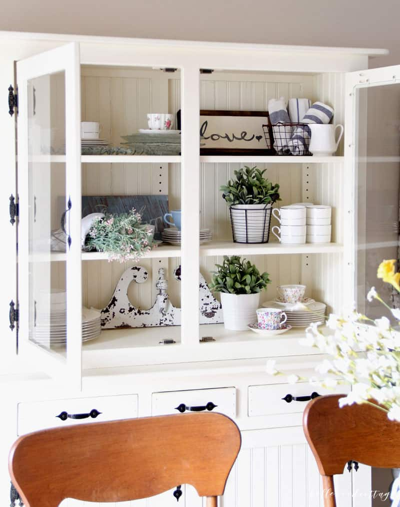 A chalk painted white hutch filled with antiques and home decor.