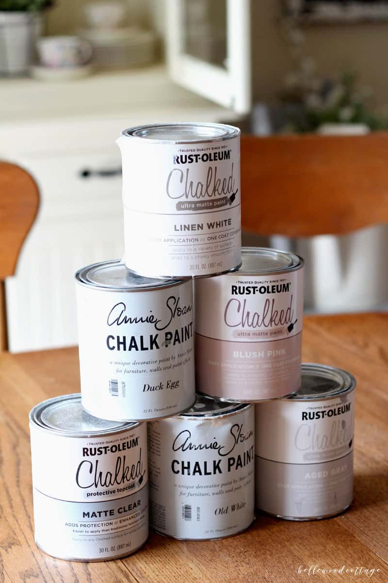 Six cans of chalk paint on table.