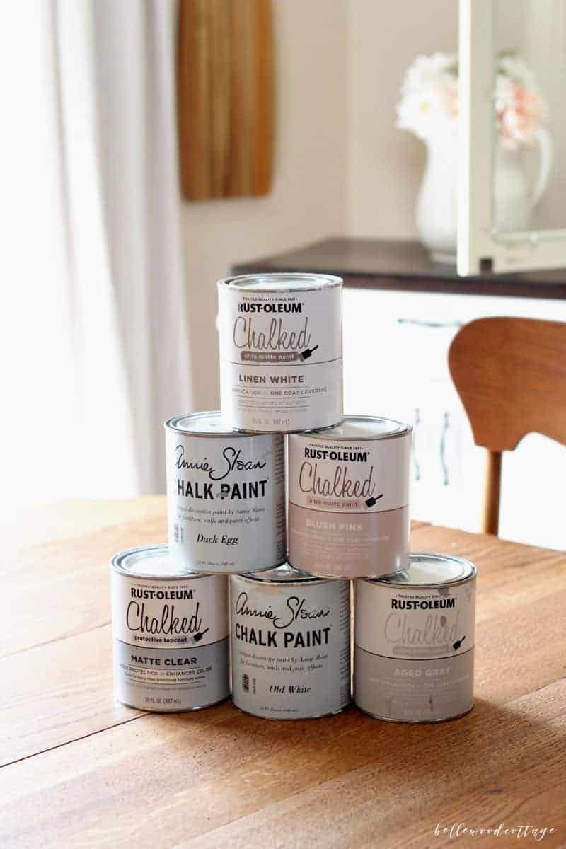 Six cans of chalk paint stacked on a table.