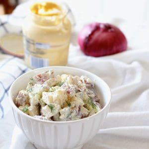 Bowl of potato salad with red onion and Dijon mustard in background.