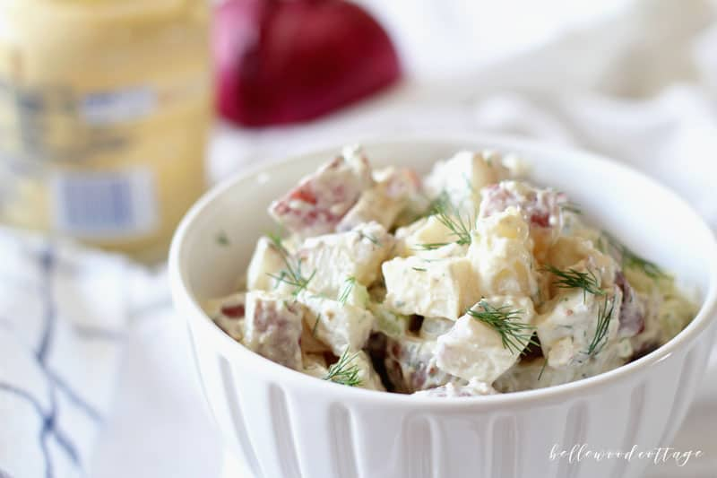 A white bowl filled with potato salad and garnished with dill.