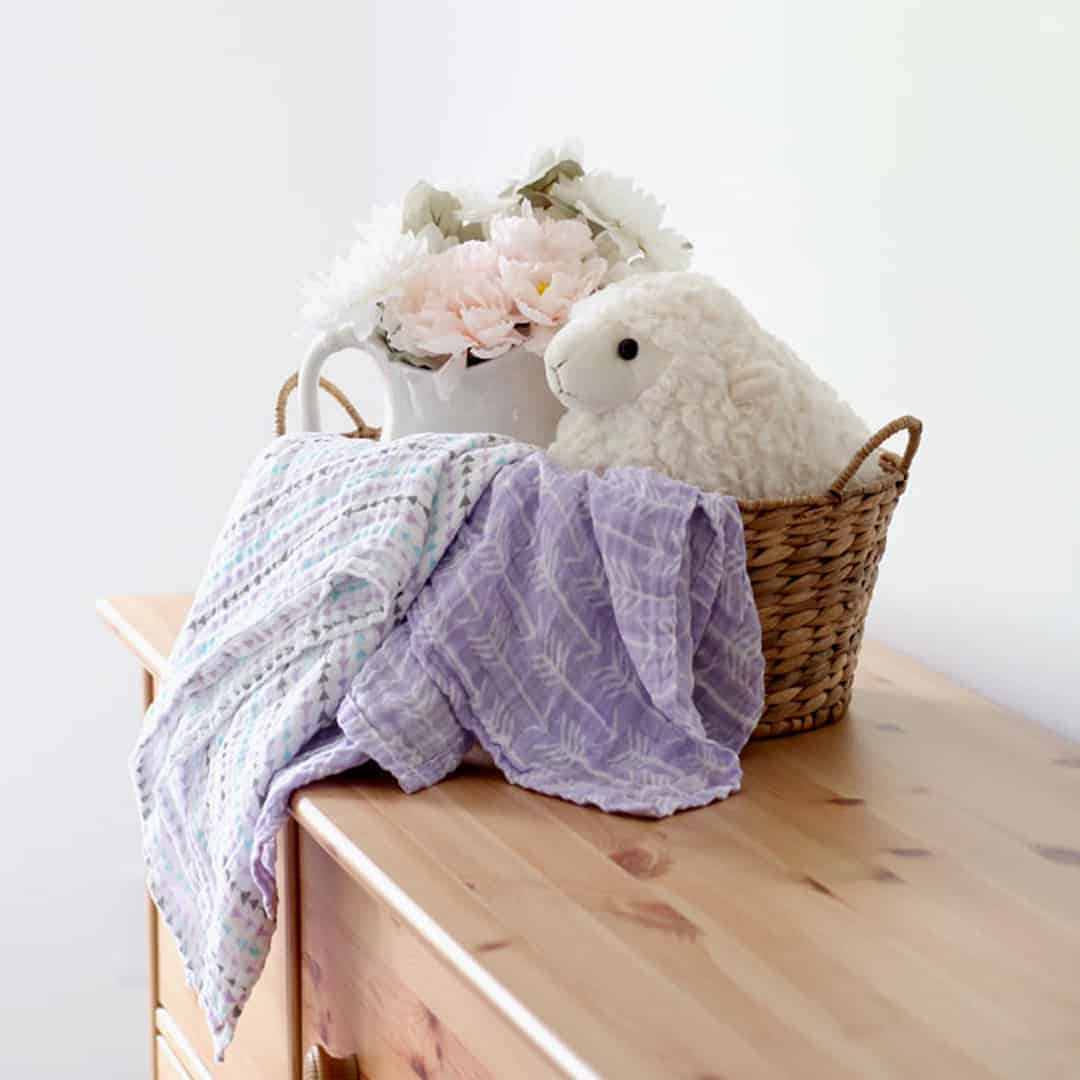 DIY muslin swaddle blankets in a woven basket.