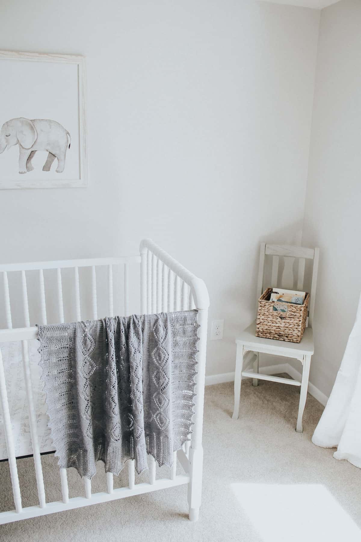 Hand knit blanket on a white Jenny Lind crib.