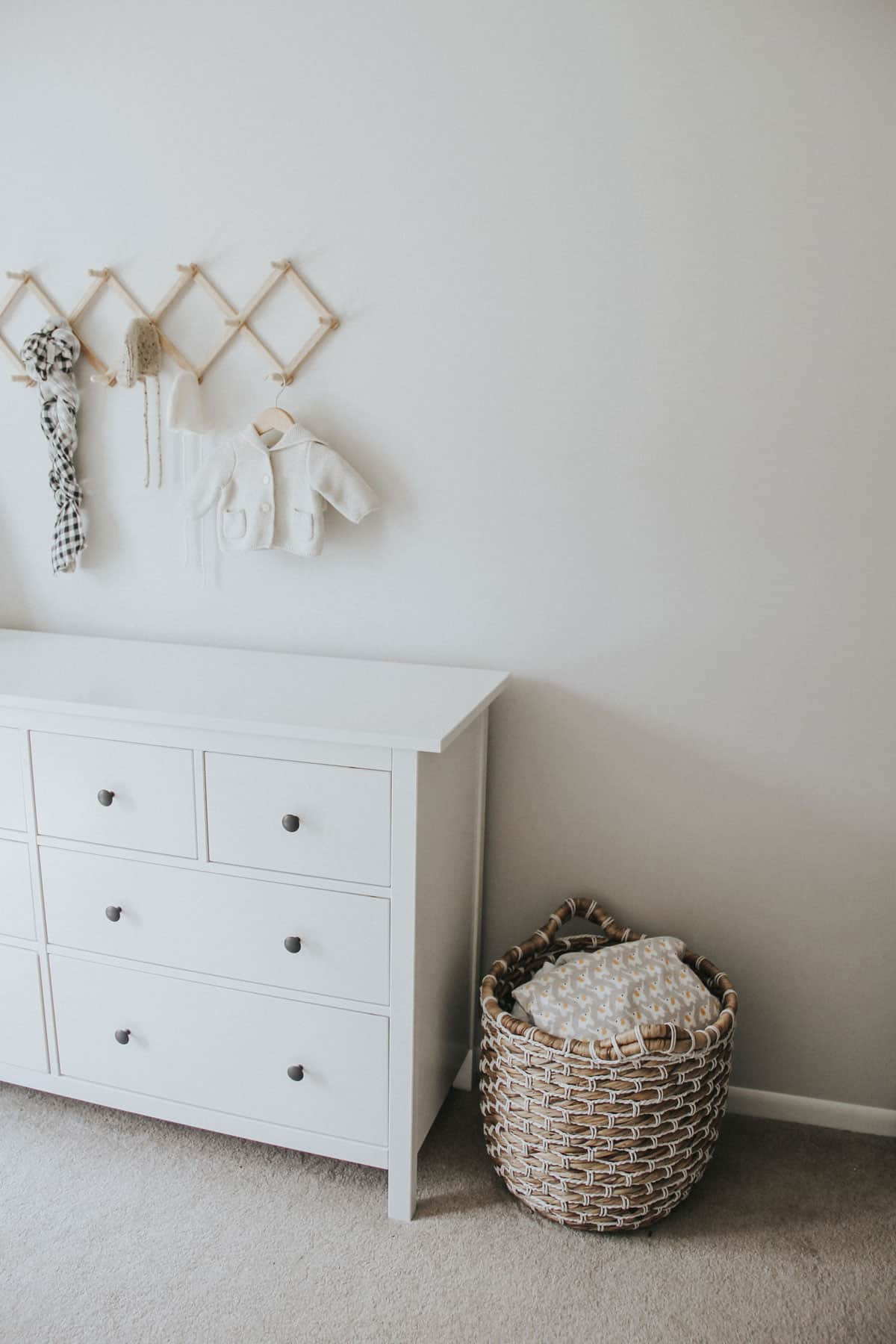 Large basket filled with baby blankets alongside a white Ikea dresser in a neutral baby room.