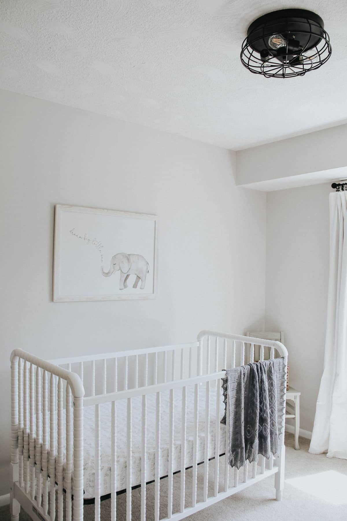Jenny Lind crib with knitted blanket in a neutral nursery with a farmhouse light.