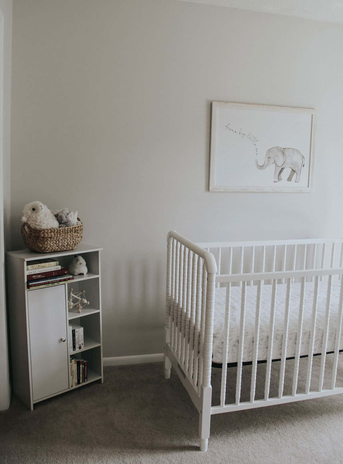 Baby bookshelf, stuffed animals and a white Jenny Lind crib in a nursery.