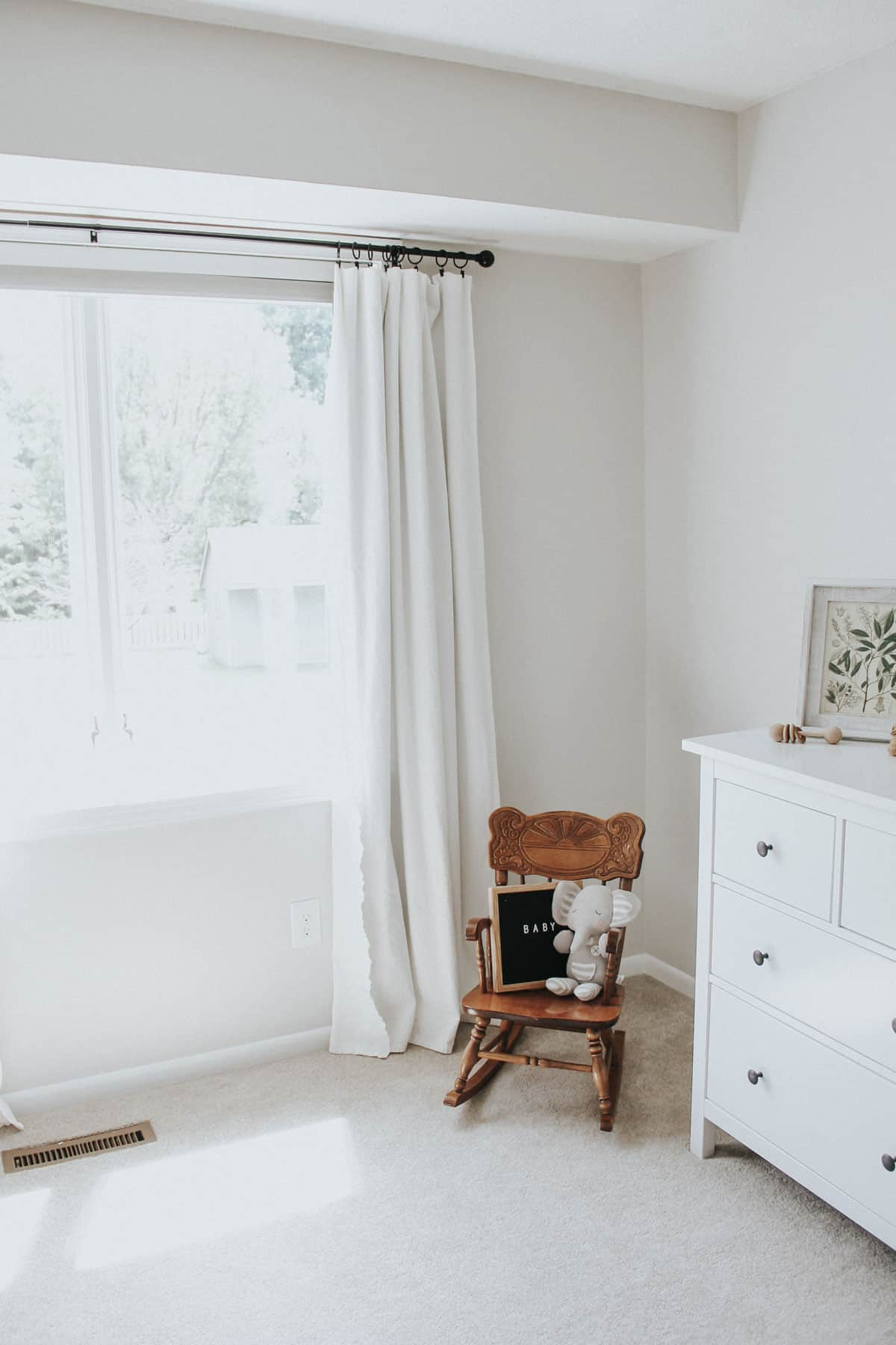 Bleached drop cloth curtains, rocking chair, and dresser in a neutral nursery.