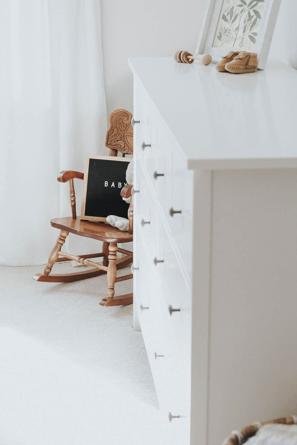 Rocking chair, letter board, and white dresser in a neutral nursery.