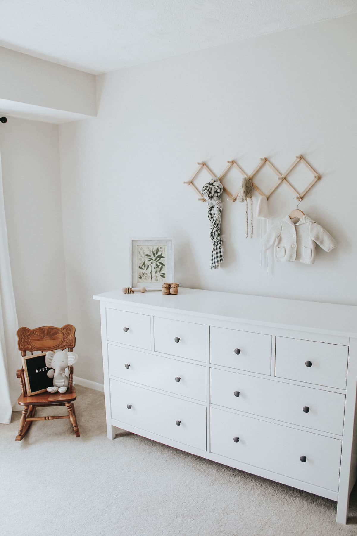 Rocking chair, white dresser, and wall rack with baby garments in a neutral baby room.