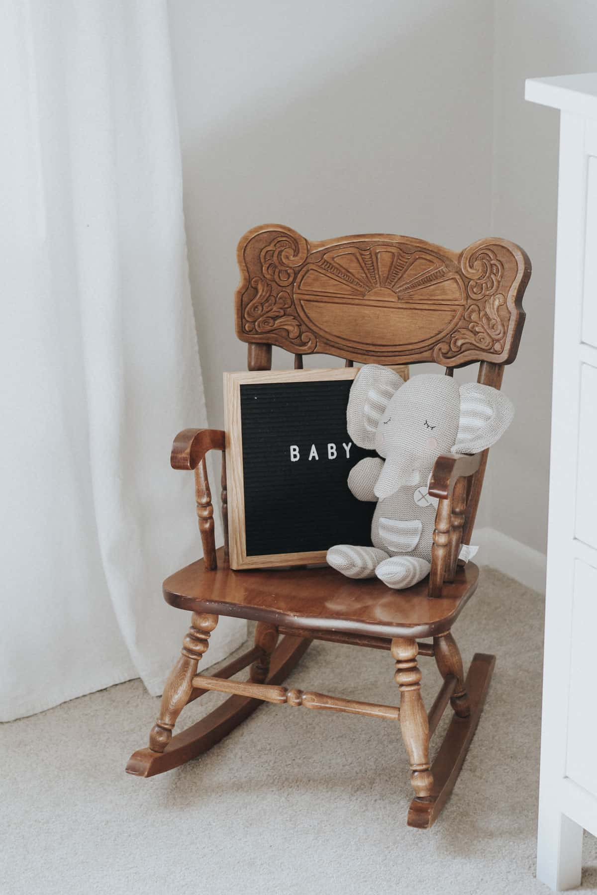 Vintage baby rocking chair in a gray room.