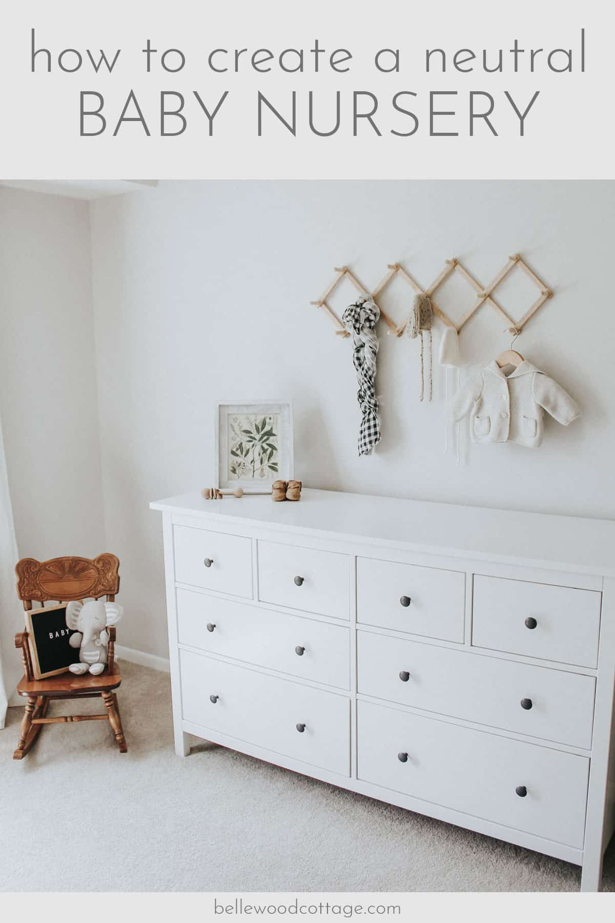 Rocking chair, white dresser, and wall rack with baby garments in a neutral nursery.
