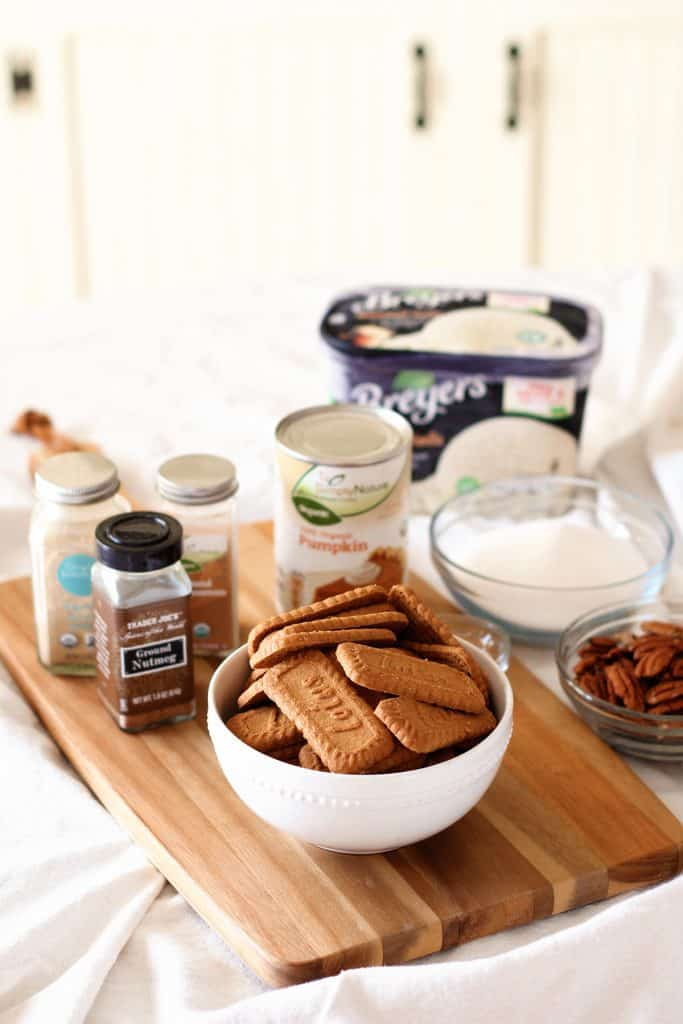 A bowl of ginger cookies surrounded by more ingredients including sugar, vanilla ice cream, and spices.