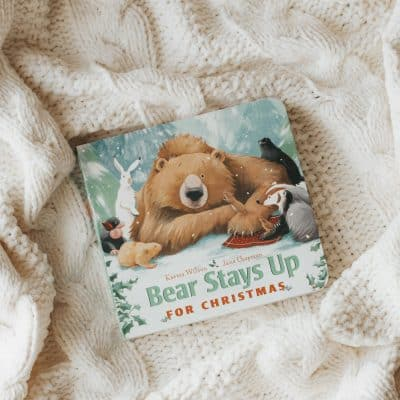 A book, Bear Stays Up for Christmas, on a cream colored blanket.