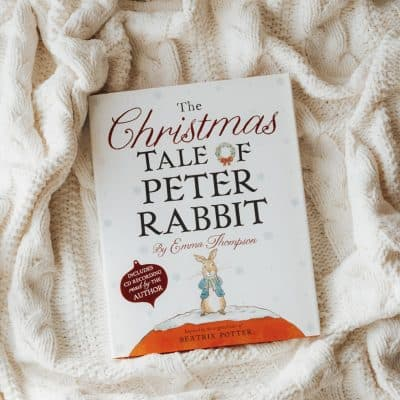 A book, The Christmas Tale of Peter Rabbit, on a cabled blanket.