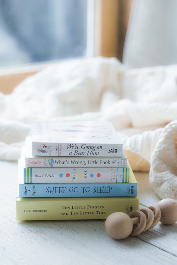 Stack of classic board books with a wooden rattle.