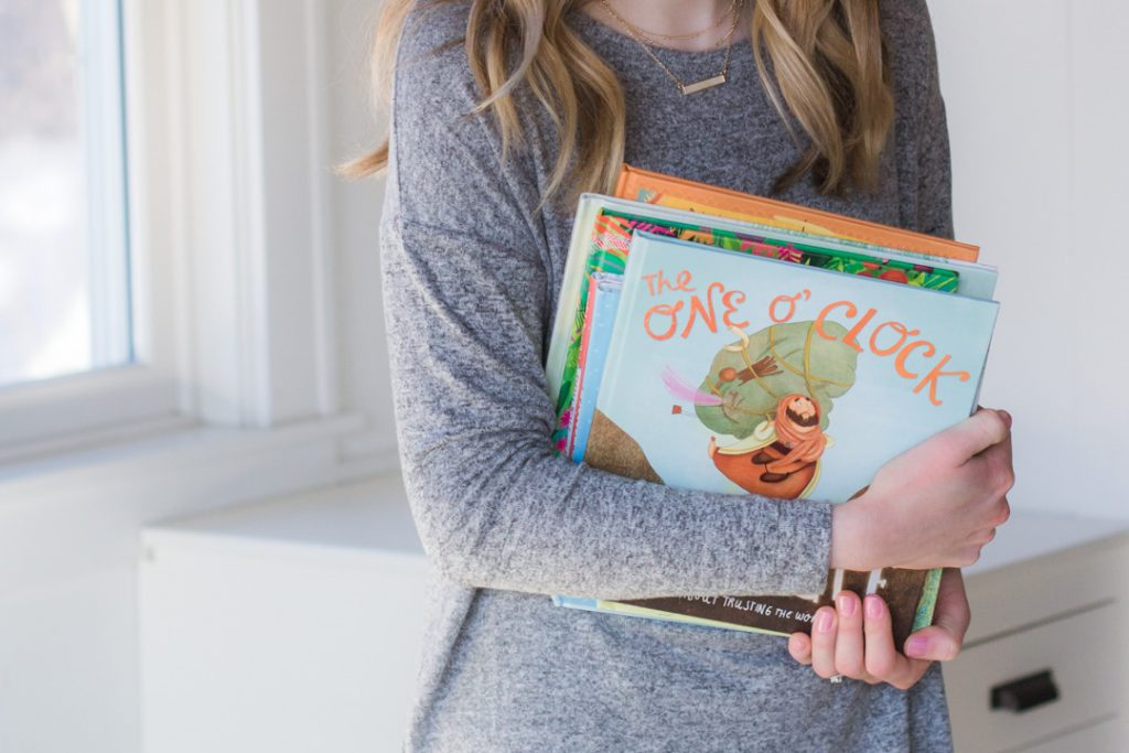 Holding a stack of picture books—part of the best picture book booklist for kids.
