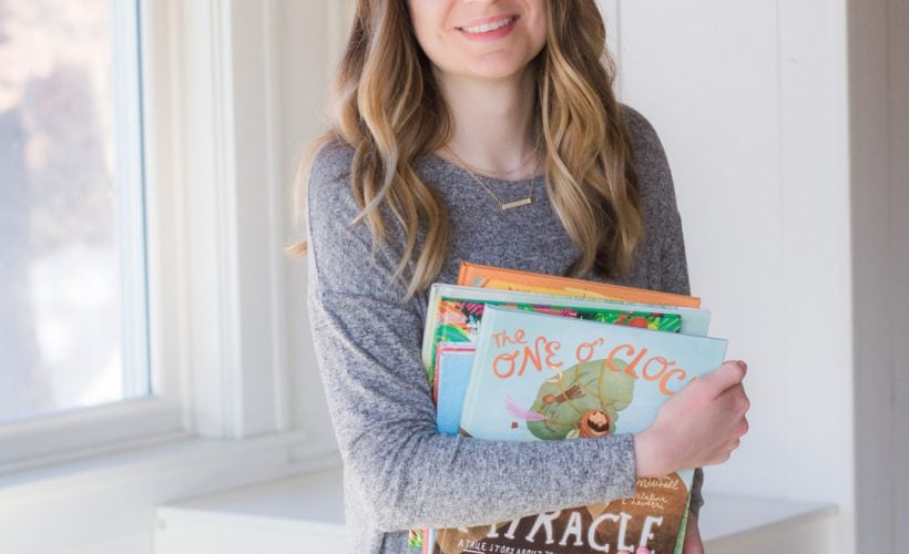 Holding a stack of colorful picture books.