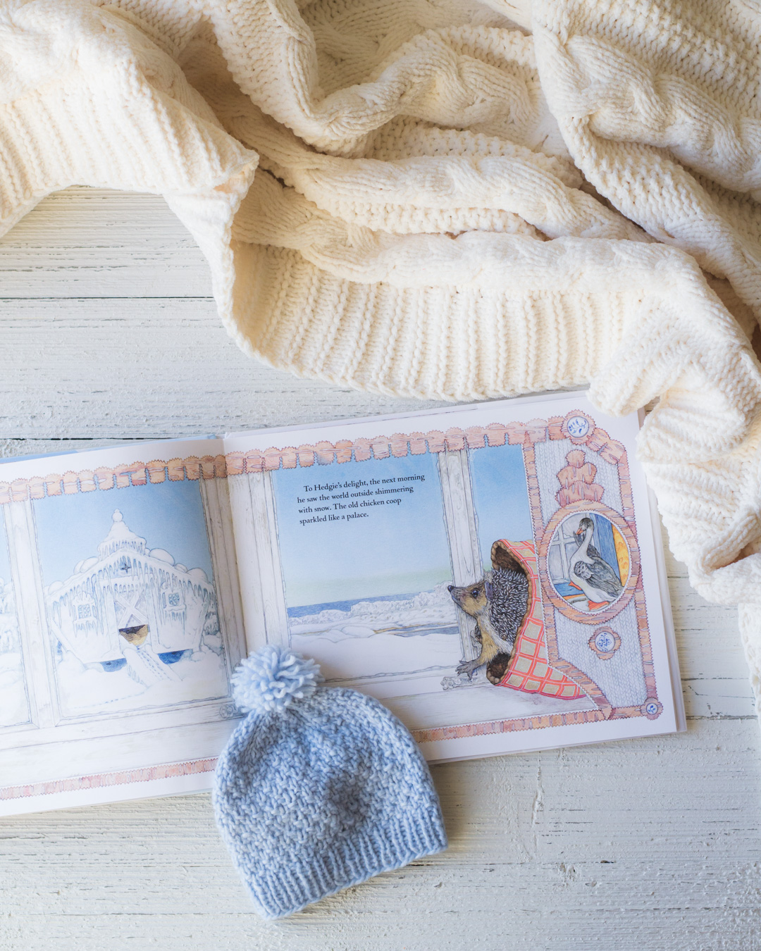 The Snowy Nap book on a wooden surface with a blanket and blue knit hat.