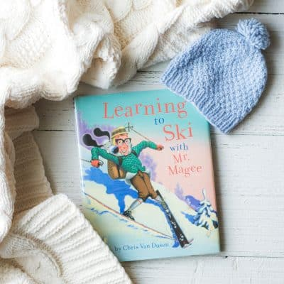 Picture book, Learning to Ski with Mr. Magee, on a wooden surface surrounded by a hat and blanket.