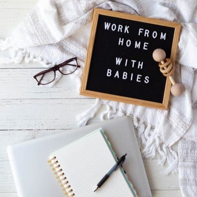 "A letterboard with the words ""work from home with babies"", a laptop, and notebooks on a wooden surface."