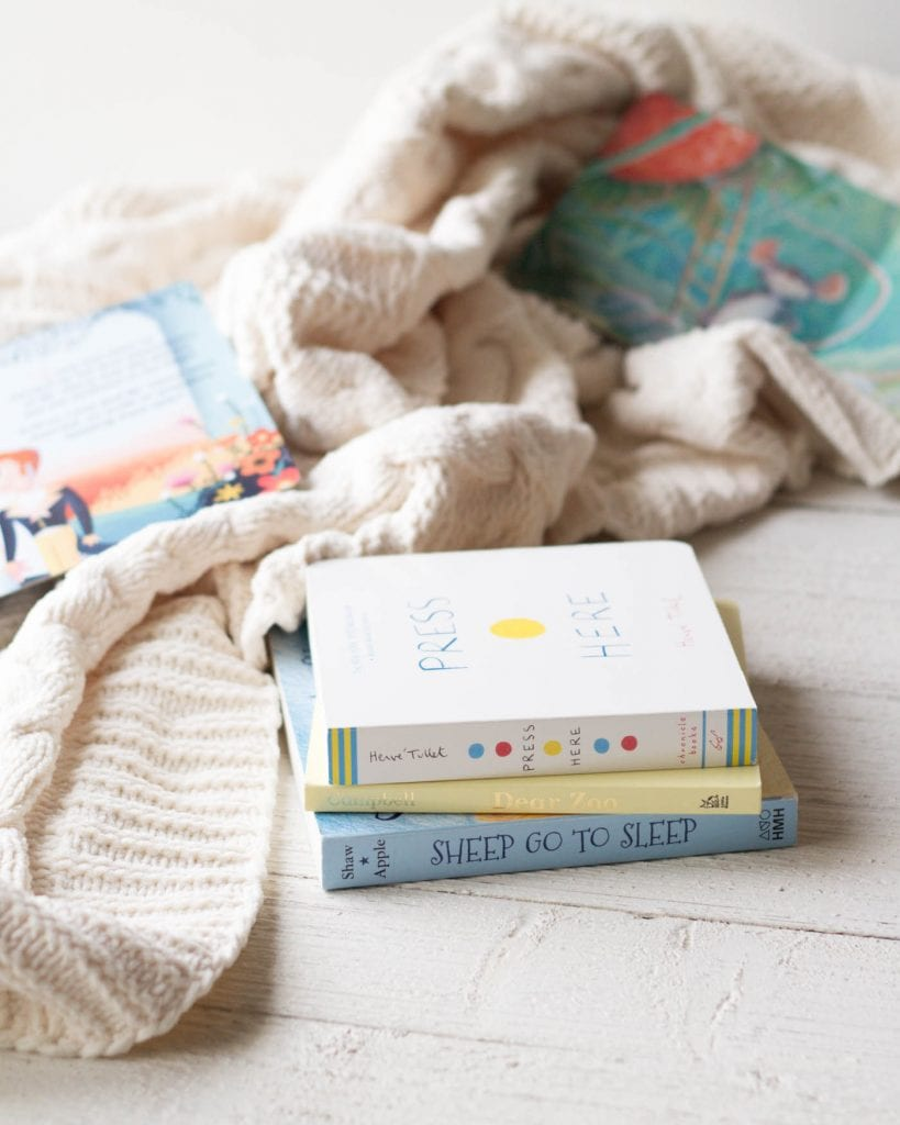 Three board books for babies on a wooden surface surrounded by a knit blanket.