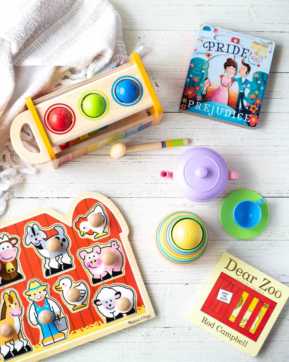 Educational toys under $25 for one-year-olds including, toddler puzzles, stackers, books, and a xylophone on a wooden surface.