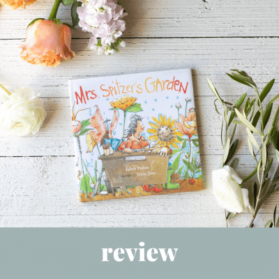 Mrs. Spitzer's Garden picture book on a wooden surface surrounded by flowers.