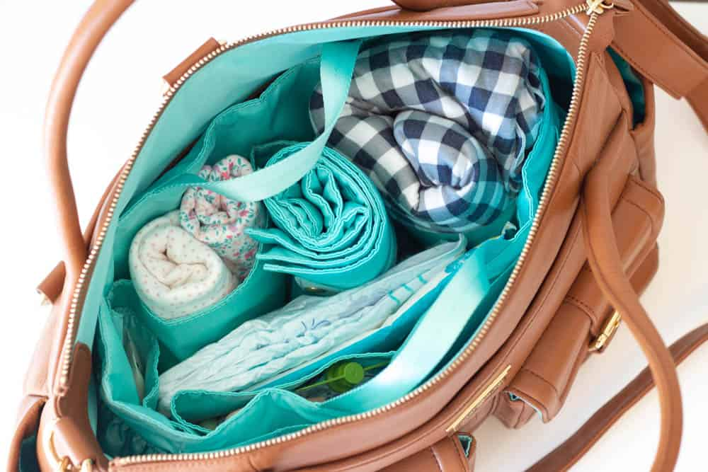 An interior view of a Lily Jade diaper bag packed with a baby wrap, extra clothing, and diapers.