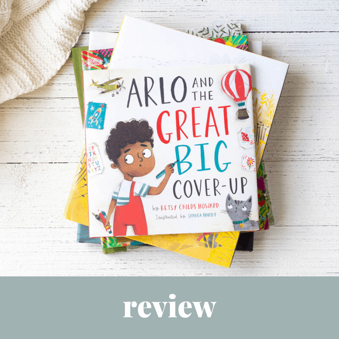 Arlo and the Great Big Cover-Up, a kids' picture book, on a wooden background.