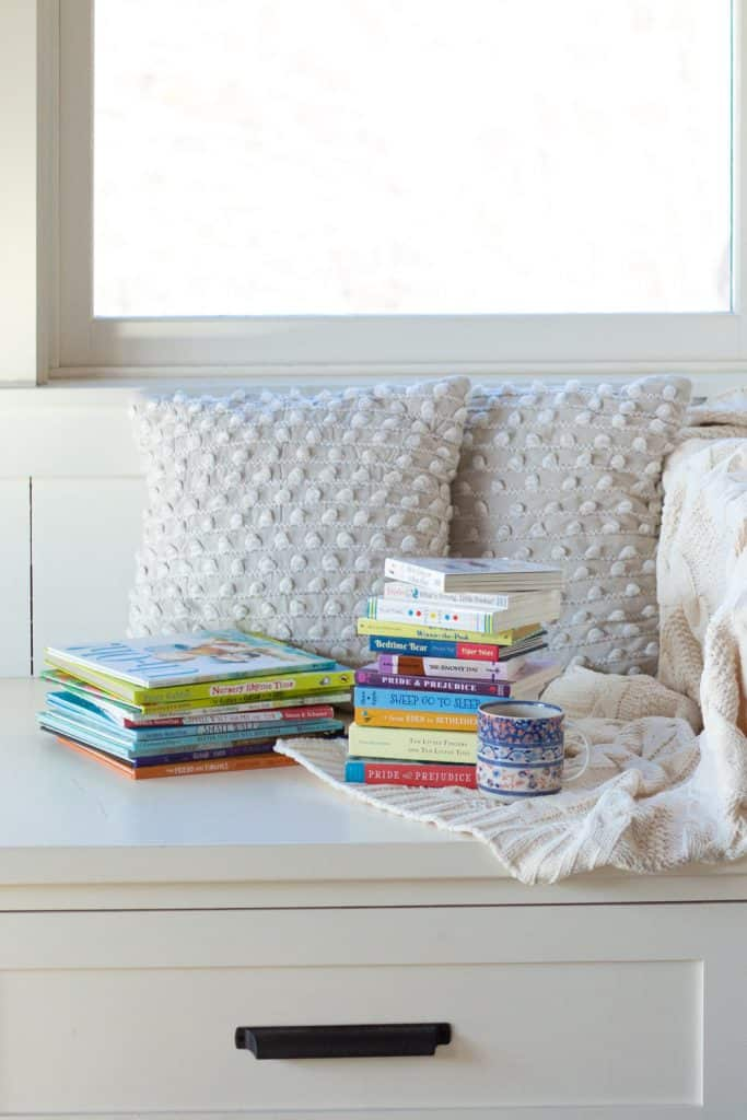Stacks of kids' books on a window seat represent how to read aloud every day with kids and babies.