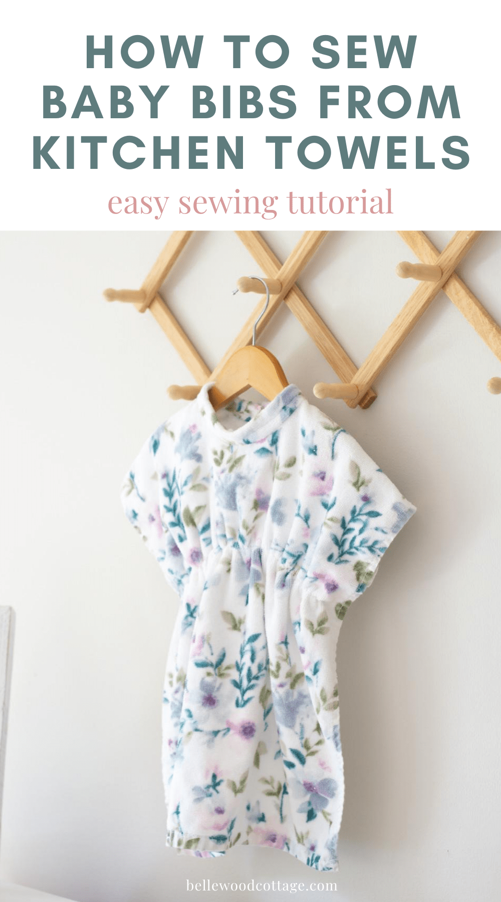 "A baby bib sewn from a kitchen towel hanging on a peg rack with the words, ""How to Sew Baby Bibs from Kitchen Towels"" above."