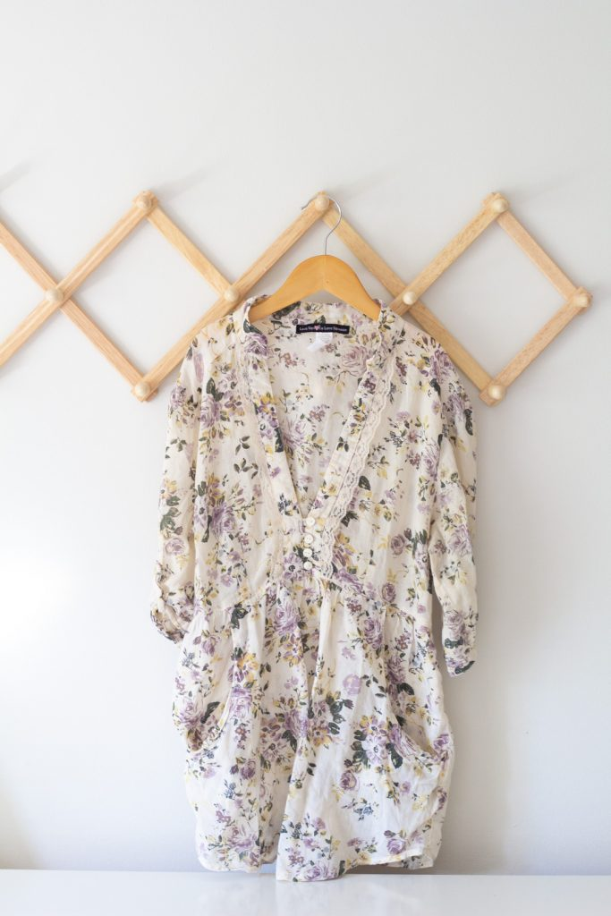 A women's blouse on a wooden hanger.