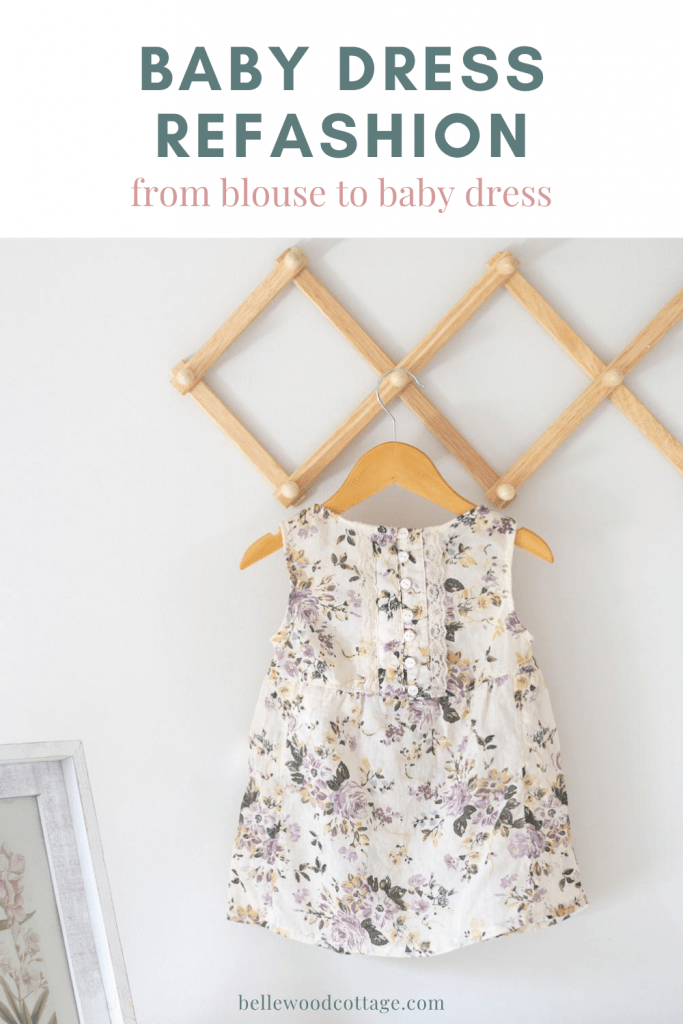 A baby dress sewn from an old blouse on a wooden hanger.