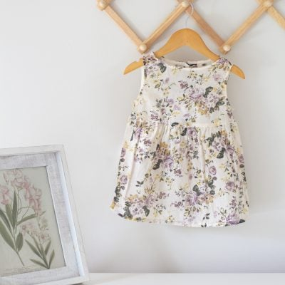 A baby dress refashion--dress on a wooden hanger.