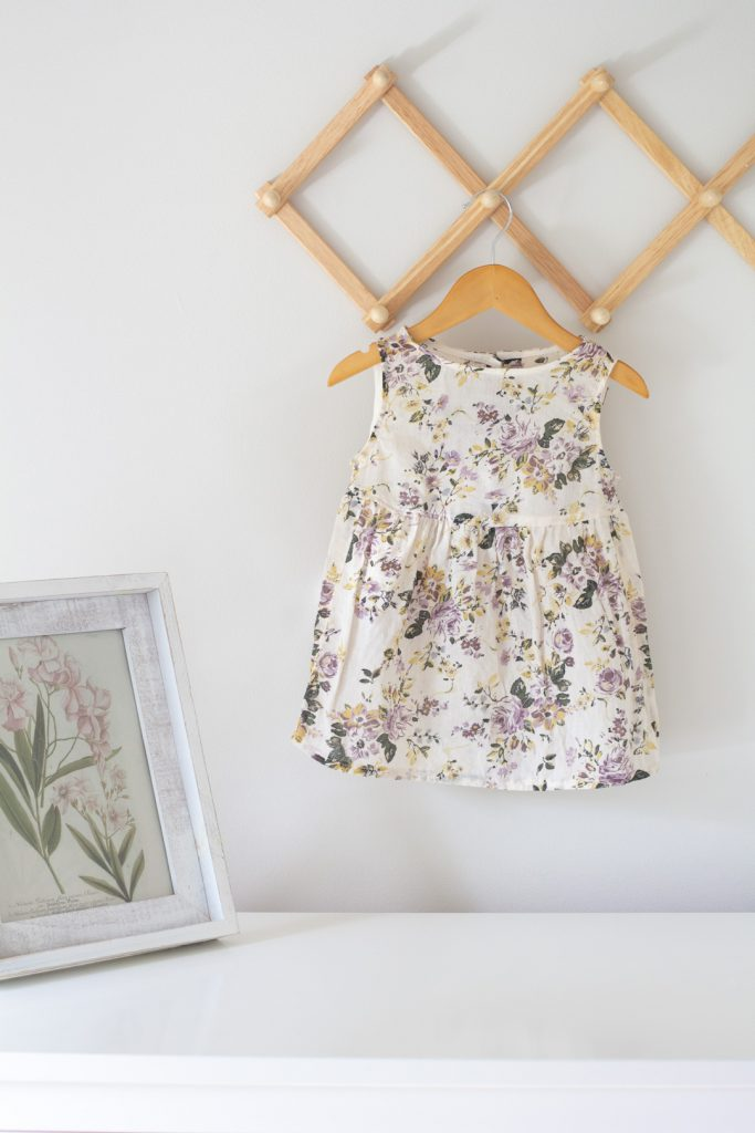A baby dress refashion -- hanging on a wooden hanger.