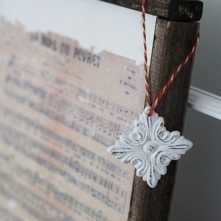 A homemade Christmas ornament hanging on the edge of a framed Christmas print.