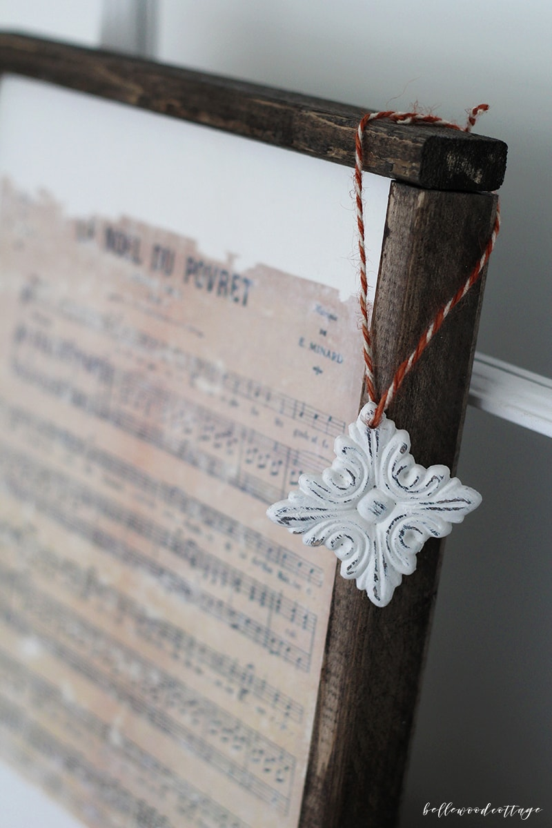 A hand-painted farmhouse ornament hanging off the edge of a framed Christmas print.