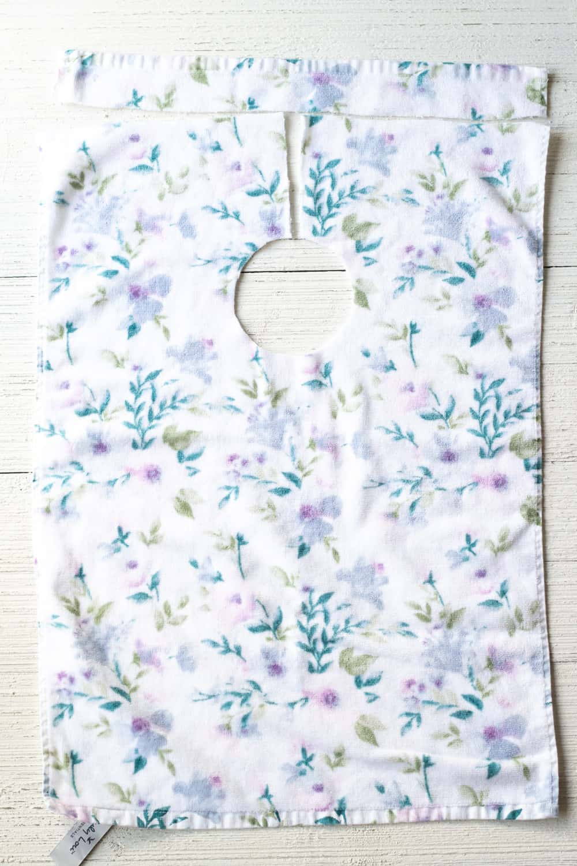 A kitchen towel cut to make a baby bib.
