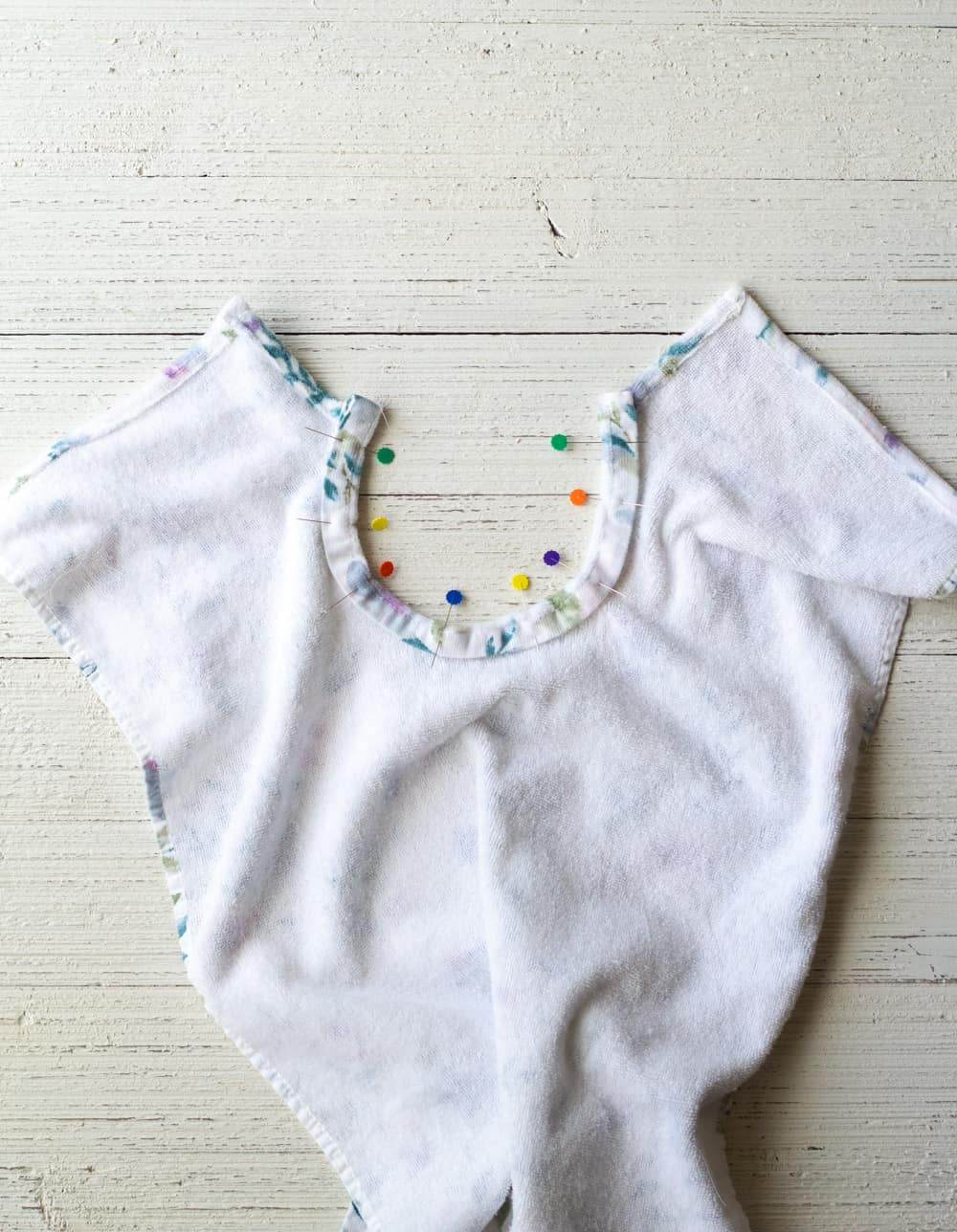 Pinning a collar down onto a kitchen towel baby bib.