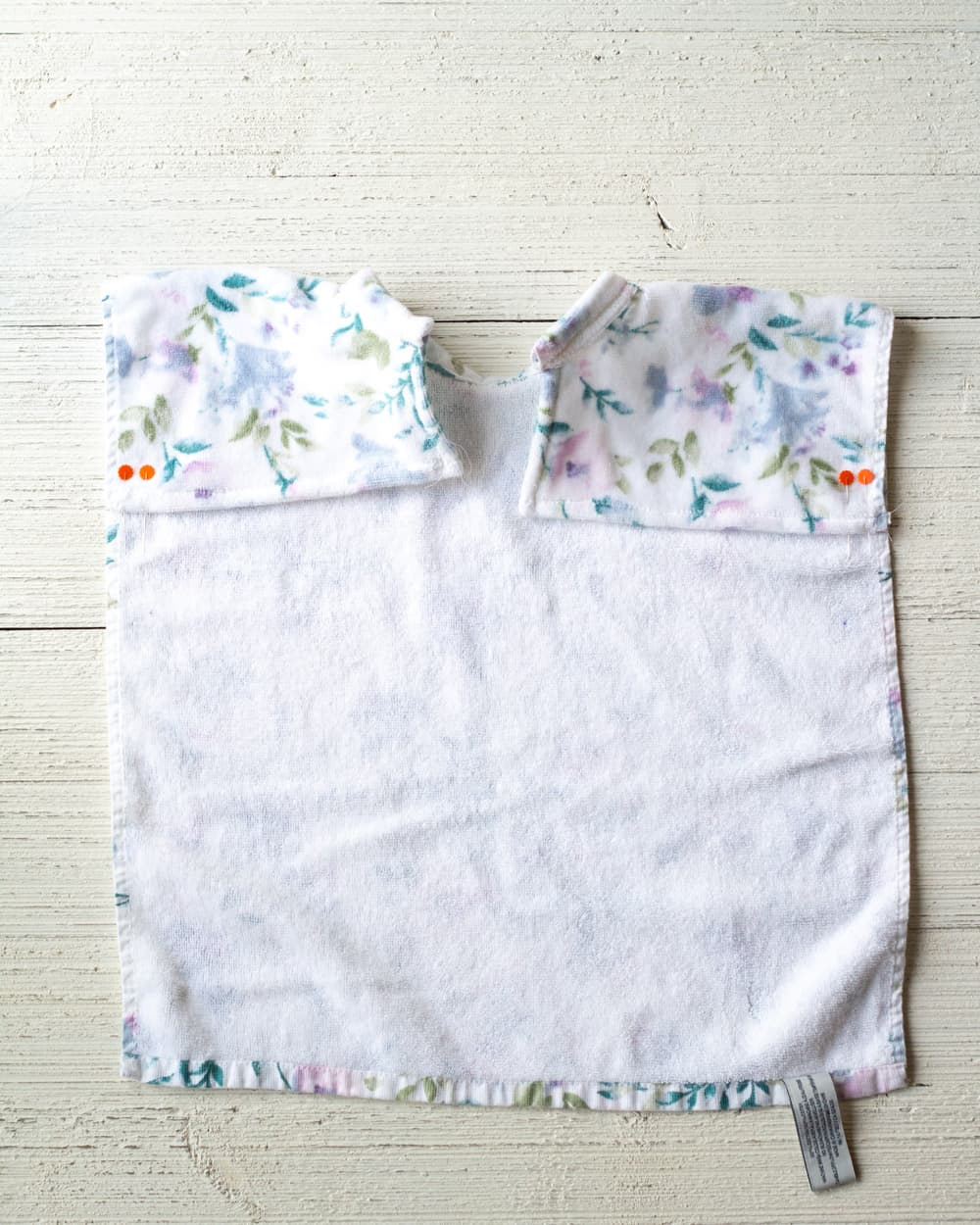 Folding down the edges of a kitchen towel to create a baby bib.